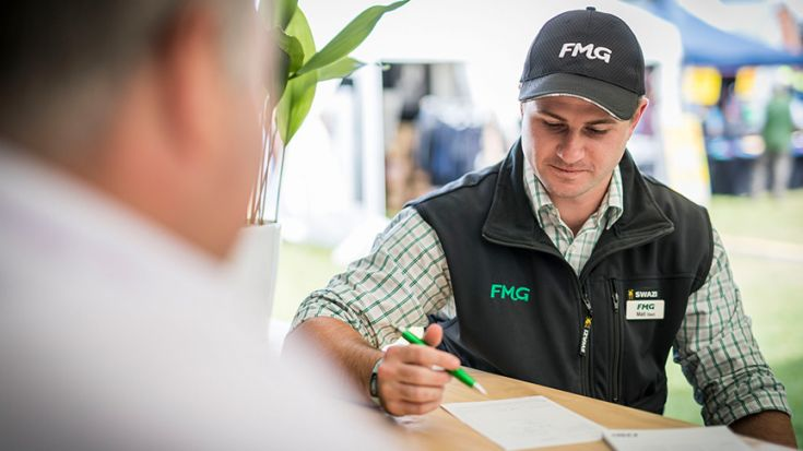 Man in FMG clothing looking at document